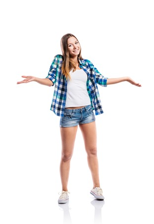 white singlet: Standing teenage girl in denim shorts , tight singlet, blue checked shirt and canvas sneakers, arms raised, young woman, isolated on white background Stock Photo