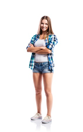 Standing teenage girl in denim shorts , tight singlet, blue checked shirt and canvas sneakers, arms crossed, young woman, isolated on white background Banque d'images