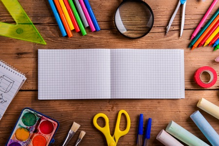 notebook paper background: Desk with various school supplies and empty squared paper notebook  in the middle . Studio shot on wooden background, frame composition, empty copy space