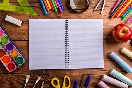 lapiz y papel: Escritorio con varios útiles escolares y cuaderno vacío papel rayado en el medio. Tiro del estudio sobre fondo de madera, la composición del marco, el espacio vacío de la copia