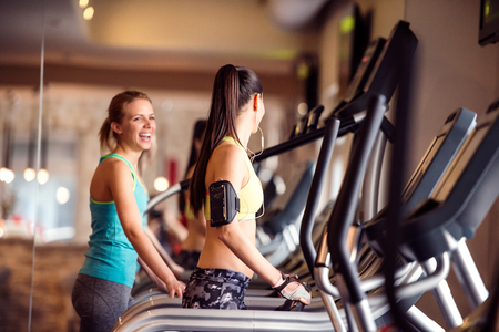 gym clothes: Two attractive fit women running in sports clothes on treadmills in modern gym