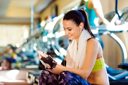 treadmill: Attractive fit woman in a gym with smart phone against a row of treadmills