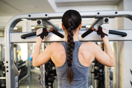 woman muscle: Close up of attractive fit woman flexing back muscles on cable machine, back view, rear viewpoint