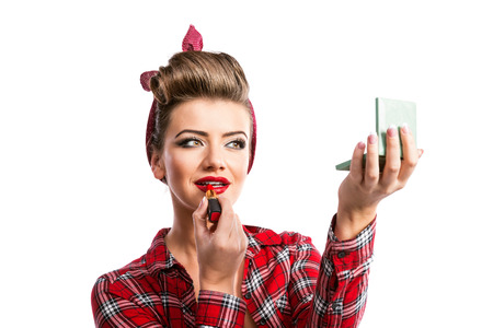 put up: Woman in red checked shirt with pin-up make-up and hairstyle holdin a mirror and applying lipstick. Studio shot on white background Stock Photo