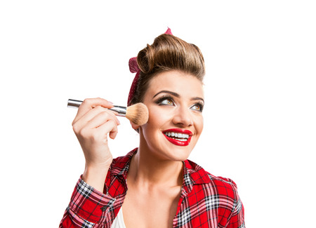 put up: Woman in red checked shirt with pin-up hairstyle applying make-up with a brush. Studio shot on white background