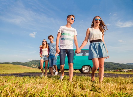 campervan: Young teenage couples in love, boy and girl, boyfriend and girlfriend, outside in green nature, against blue sky, old green campervan