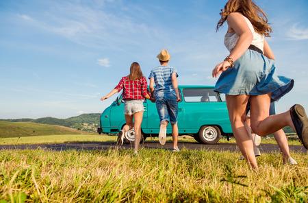Jonge tiener paren in de liefde lopen, jongen en meisje, vriend en vriendin, buiten in de groene natuur, tegen de blauwe hemel, oude camper, terug bekijken, achter gezichtspunt
