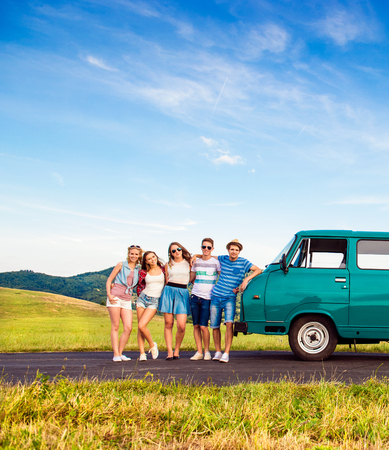 Young teenage hipster frieds with campervan against green nature and blue sky Banque d'images