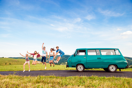 campervan: Young teenage hipster frieds with campervan against green nature and blue sky, jumping