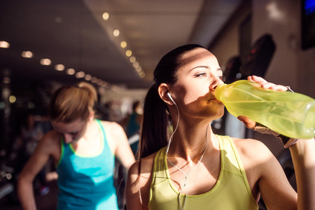 Attractive fit woman in gym drinking water from bottle, sunny day Zdjęcie Seryjne