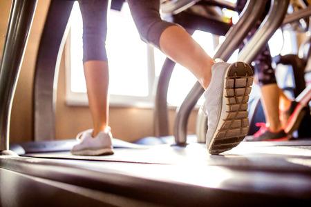 Đóng lên chân của người phụ nữ đang chạy trên máy tập chạy bộ tập thể dục, ngày nắng