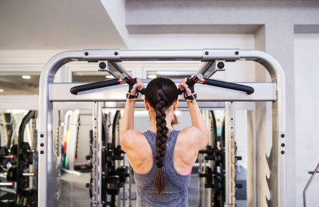 back to work: Close up of attractive fit woman flexing back muscles on cable machine, back view, rear viewpoint