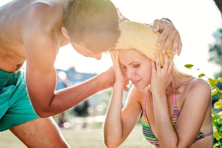 dolor de cabeza: Hombre joven que ayuda a la mujer en bikini con un golpe de calor, el calor del verano, día soleado Foto de archivo