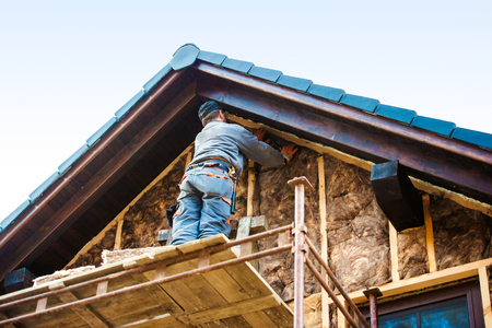 建設労働者が足場熱絶縁グラスウールと家の正面に立っています。