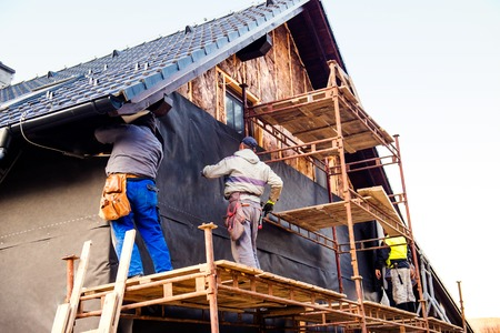 heights job: Construction workers standing on scaffold thermally insulating house facade with glass wool and black foil.