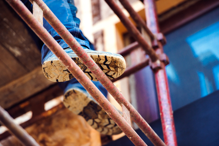 Close up of legs and soles of unrecognizable man standing on scaffold