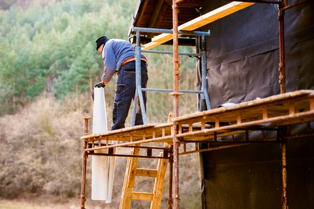 rockwool: Construction worker standing on scaffold thermally insulating house facade, putting black foil on