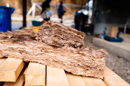 rockwool: Pieces of glass insulation wool laying on wooden beams laying on construction site Stock Photo