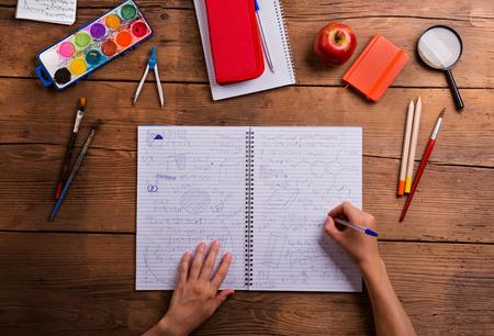 hombre escribiendo: Manos del hombre escribiendo en el bloc de notas con los símbolos matemáticos y fórmulas. Vaus útiles escolares, para establecer planos. Estudio tirado en el fondo de madera.