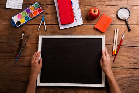 kugelschreiber: Hände des Mannes leer schwarzes Bild zu halten. Verschiedene Schulmaterial, flach lag, Kopie, Raum. Studio Schuss auf Holzuntergrund. Lizenzfreie Bilder