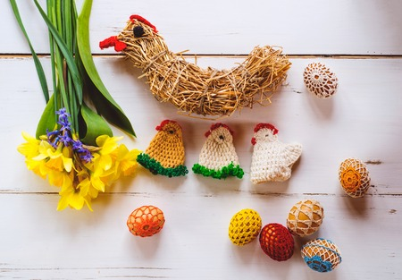 set up: Crocheted Easter eggs, chickens, straw hen and fresh daffodil bouquet against white wooden background. Easter composition. Stock Photo
