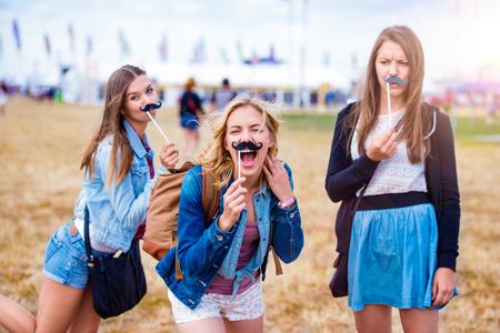 偽の口ひげを楽しんで夏の音楽祭で 10 代の少女 写真素材