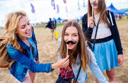 chicas adolescentes: adolescentes en el festival musical de verano que se divierte con bigote falso