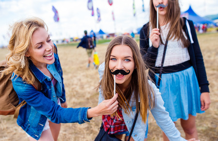 laughing girl: Teenage girls at summer music festival having fun with fake mustache