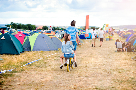 Teenage boy and girl having fun riding bike together at summer music festival in a tent sector, back view, rear viewpoint