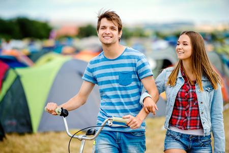 mezclilla: adolescente y una niña en el amor con la bicicleta en el festival de música de verano en un sector de tienda de campaña