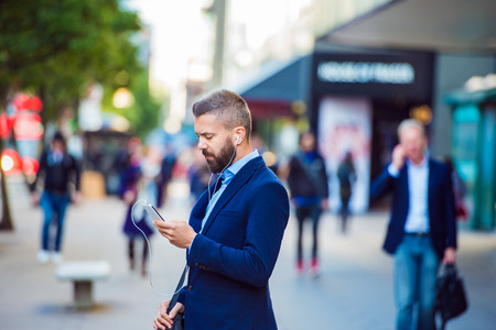 phone business: Hipster manager holding a smartphone texting and listening music outside in the street