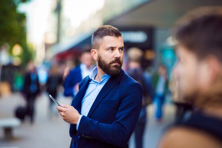 crowded street: Hipster manager holding a smartphone outside in the crowded street Stock Photo