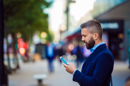 reading and writing: Hipster manager holding smartphone, texting, reading, writing, searching something, outside in the street