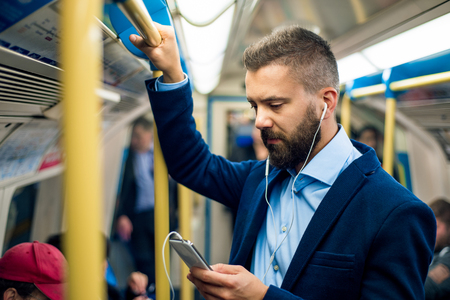 Ernstige zakenman met koptelefoon reizen naar het werk. Standend in de ondergrondse wagen, met handgreep.