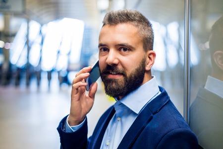 hombres jovenes: Cierre de negocios de pie inconformista con smartphone en la estaci�n de metro