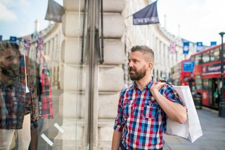 buss: Young hipster man in checked shirt shopping, holding a bag, in the streets of London, doble decker buss