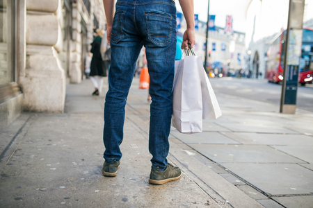 buyer: Legs of unrecognizable man with shopping bags in the crowded street of London, back view, rear viewpoint