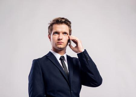 hombres jovenes: empresario inconformista joven con llamada de tel�fono de fabricaci�n de tel�fonos inteligentes. Tiro del estudio sobre fondo gris.