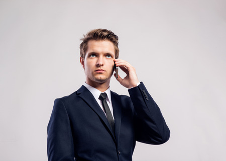 hombres jovenes: Young hipster businessman with smartphone making phone call. Studio shot on gray background.
