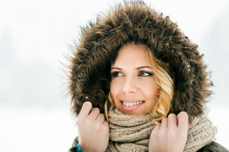fur hood: Close  up of head of blond woman in fur hood and knitted scarf, snowy winter nature