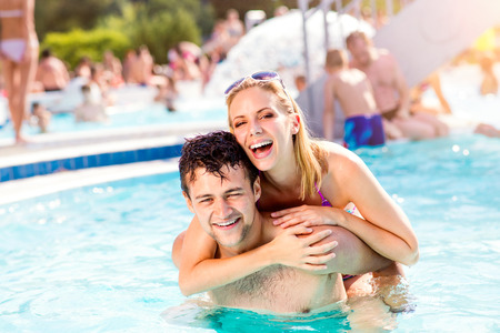 attractive couple: Man and woman in bikini on piggyback in the swimming pool, with baloon. Summer heat, sun and water. Stock Photo