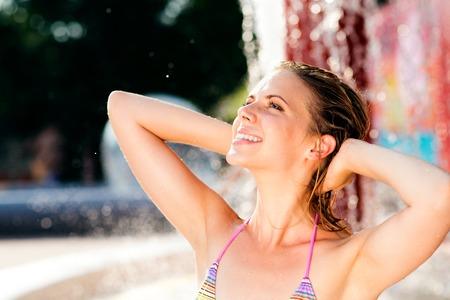 wet: Mujer en bikini de la diversión que tiene en la fuente salpicaduras. El calor del verano y el agua.