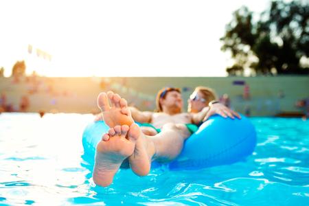 Paar in aufblasbaren Ring im Schwimmbad. Sunny Sommer, Wärme und Wasser. Schließen von Füße hoch, barfuß.
