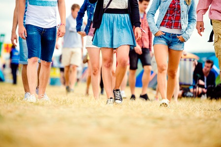 denim skirt: Unrecognizable teenagers at tent music festival walking, sunny summer, close up of legs