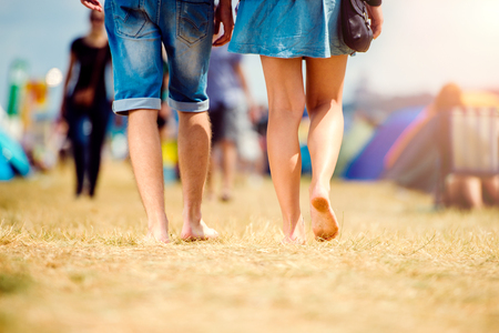 Unrecognizable teenage couple at tent music festival walking, sunny summer, close up of legs, back view, rear viewpoint Stock Photo