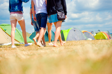 barefoot teens: Unrecognizable teenagers at tent music festival walking, sunny summer, close up of legs, back view, rear viewpoint