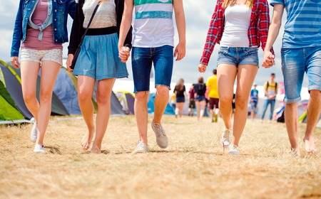 boy shorts: Unrecognizable teenagers at tent music festival walking, sunny summer, close up of legs