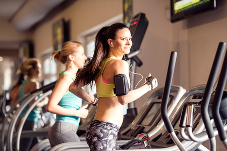 hard work: Two attractive fit women running in sports clothes on treadmills in modern gym