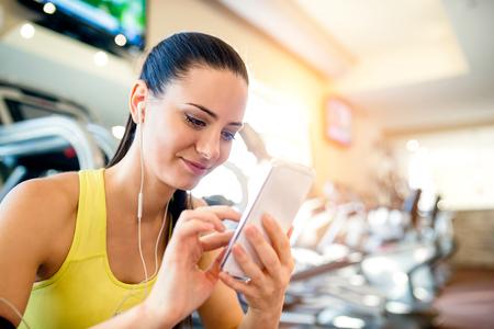 Aantrekkelijke geschikte vrouw in een sportschool met slimme telefoon tegen een rij van loopbanden Stockfoto
