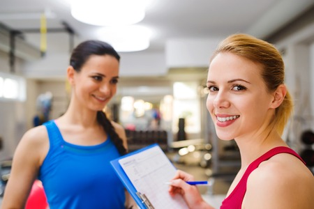 work out: Close up, attractive fit woman in a gym consulting  work out with personal trainer, exercise plan on clipboard